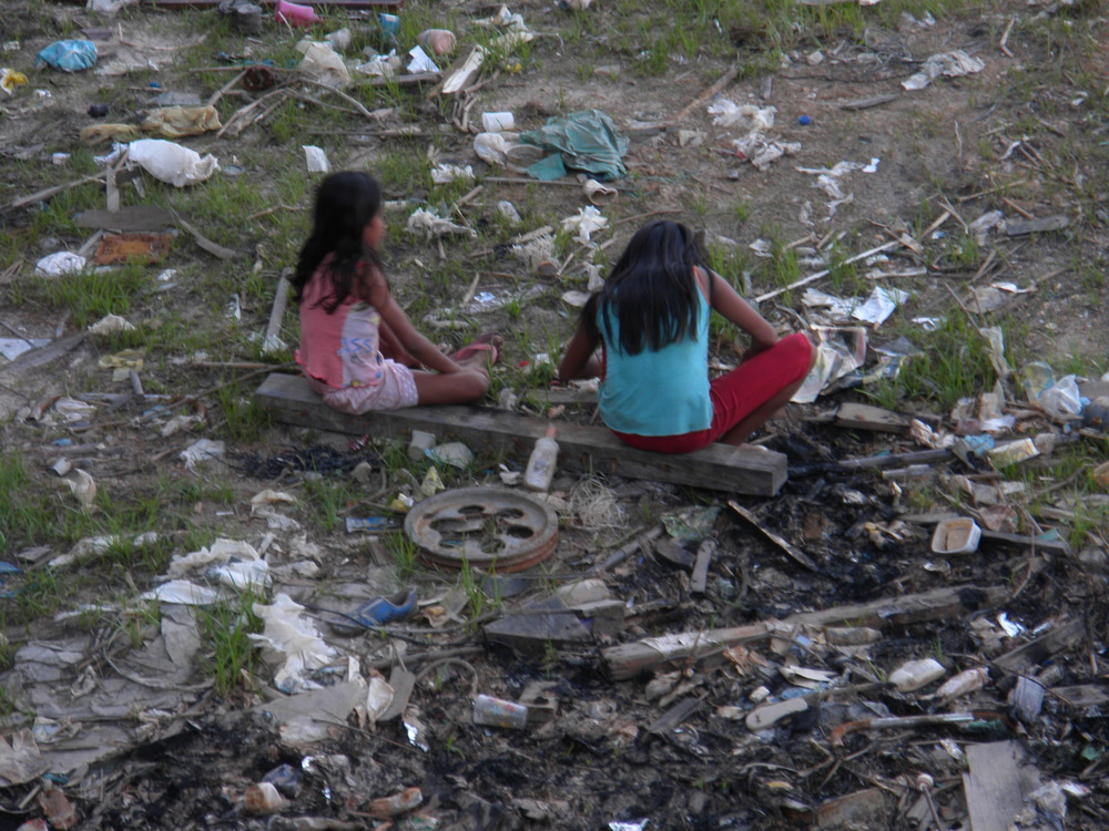 Young girls sitting in trash in an inlet of the Rio Negra